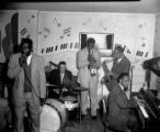 Five-man African-American band (piano, trumpet, drums, saxophone and singer), on stage at the Elks...