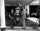 Couple standing by a gasoline pump at T.C. Gilbert, Jr's Gulf Station