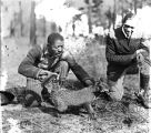 African American men releasing a fox for the hunt, Georgia, 1931.