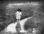 Young girl wading in a brook.