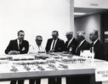 W. J. Usery and other officials stand around proposed model, 1965